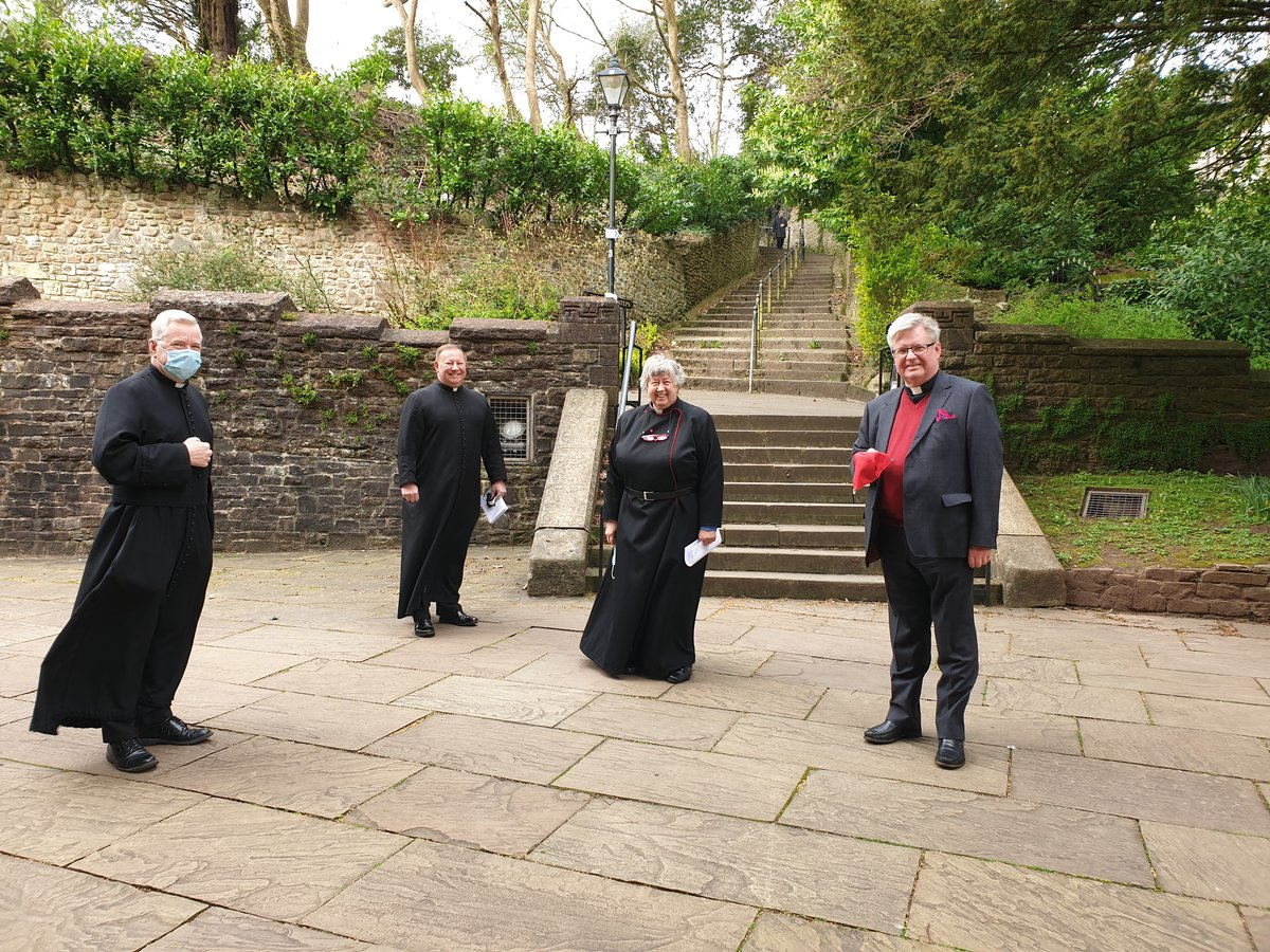 Four socially-distanced clergy outside of Llandaff Cathedral