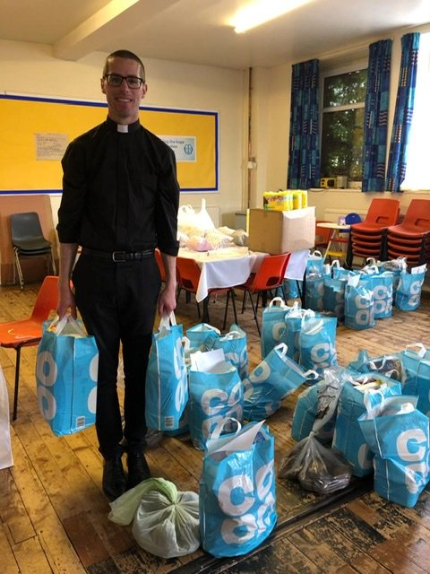 Priest holding a load of shopping bags to give away