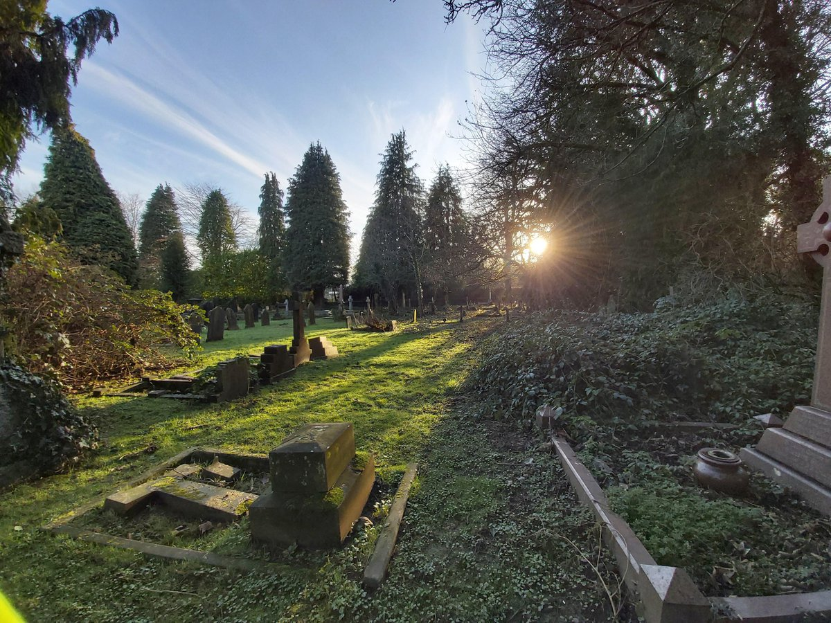 A view of the sun setting over a churchyard