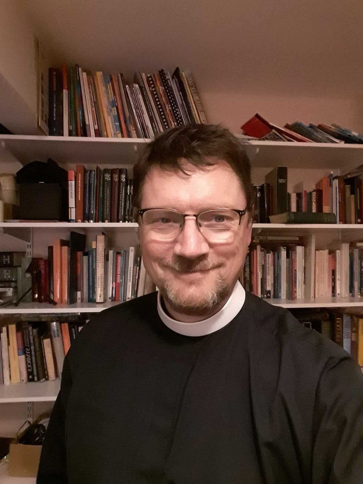 Tim Jones, smiling, wearing glasses and a cassock