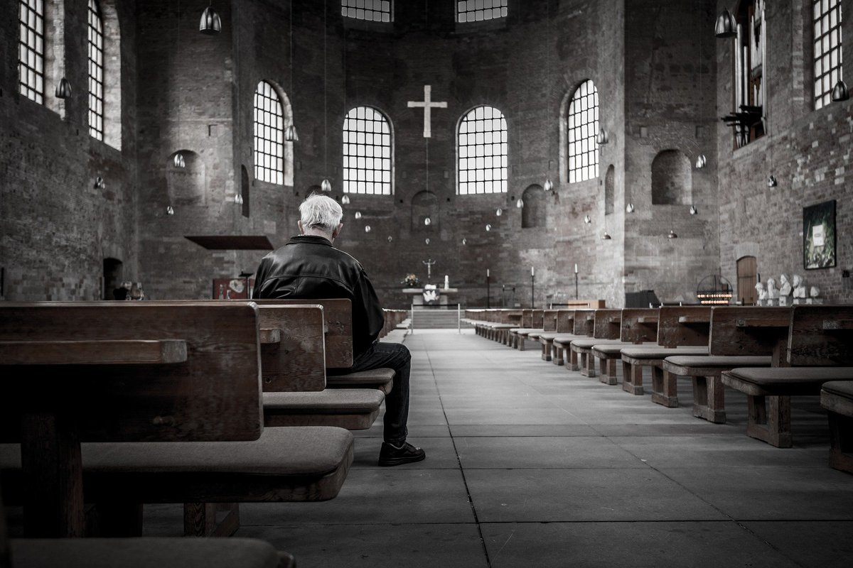 A man sitting alone in a dark church