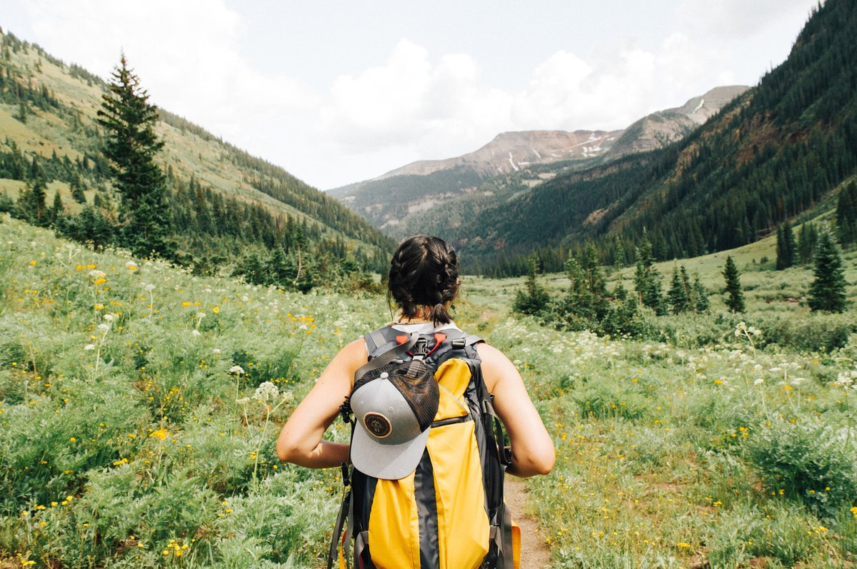 A journeying girl with a backpack looking out at a beautiful valley
