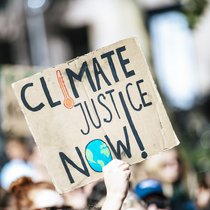 Sign at a rally reading 'Climate Justice Now'