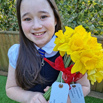 young girl holding daffodils.png